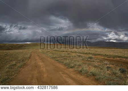 Amazing Rainbow On A Dark Stormy Sky With Thunderclouds And Rain Over The Mountains And A Dirt Road