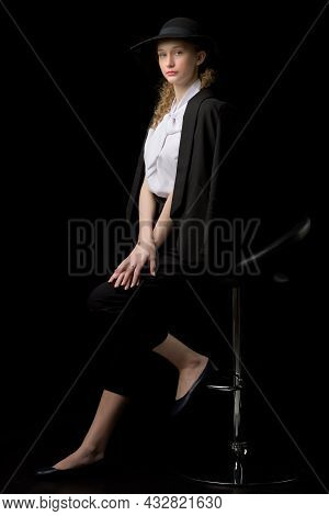 Stylish Girl In Black Suit Sitting On High Chair. Portrait Of Beautiful Young Girl Teenager In Elega