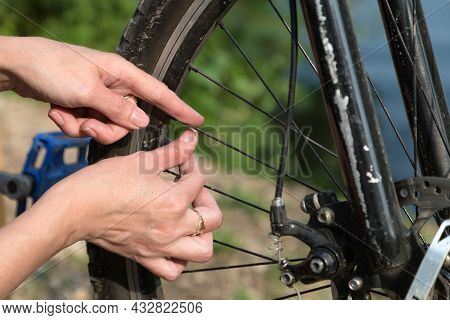 Women Hands Between The Spokes On The Rim Of The Wheel Bicycle Repair Concept.