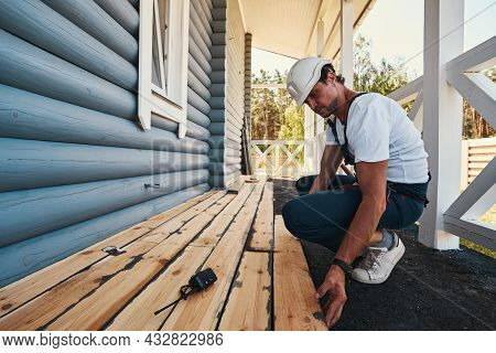 Housebuilder Is Laying Floorboards On House Porch