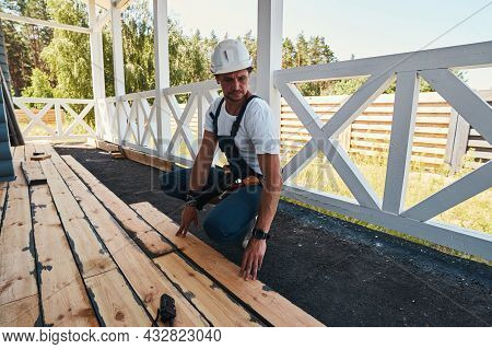 Builder Squatting And Pressing Floorboard To Porch Ground