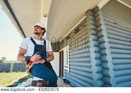 Builder Resting On Porch Railing After Finishing Work