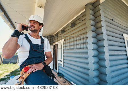 Male Housebuilder Speaking On Walkie Talkie From Porch