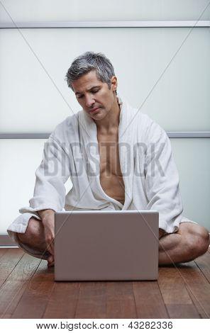 Man Wearing Bathrobe And Using A Laptop