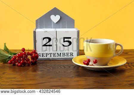 Calendar For September 25 : The Name Of The Month In English, Cubes With The Number 25, A Yellow Cup
