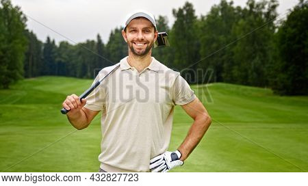 Young man with golf club looking at camera at golf course outdoors