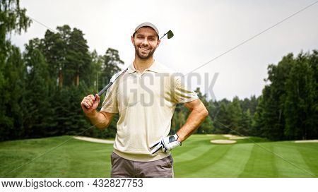 Young man with golf club looking at camera at golf course