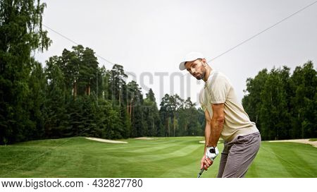 Young man in uniform playing golf on the field