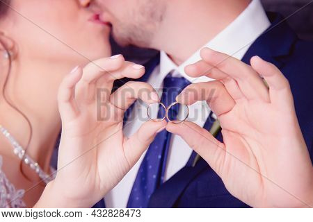 The Bride And Groom Are Holding Wedding Wedding Rings With Their Own Hands And Kissing In The Backgr