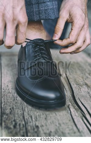 Man Ties His Shoelaces On Black Patent Leather Shoes On Old Wooden Floor, Toned Image