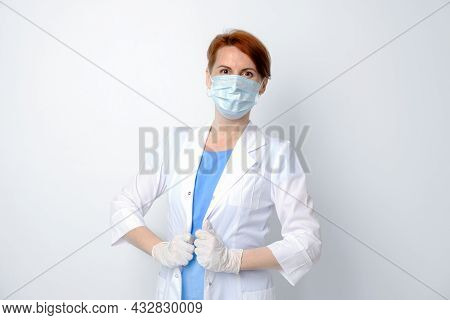 Young Woman In White Medical Gown And Protective Mask. Portrait Of Female Doctor On White Background