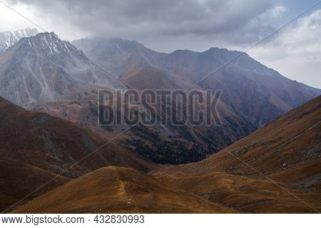 Mountain Gorge In Autumn In The Fog, The Slopes Of The Mountains Are Covered With Yellow Grass And F
