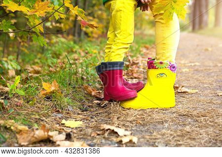Feet In Red And Yellow Rubber Boots Of A Mother And Daughter In The Autumn Forest. Seasonality, Seas