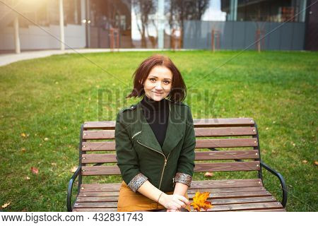 A Woman With A Bob Haircut And A Yellow Fallen Maple Leaf In A Green Jacket And A Mustard Mini Skirt