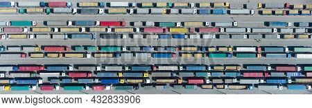 Aerial View Of Colorful Trucks In The Terminal Waiting For Unloading. Top View Of The Logistics Cent