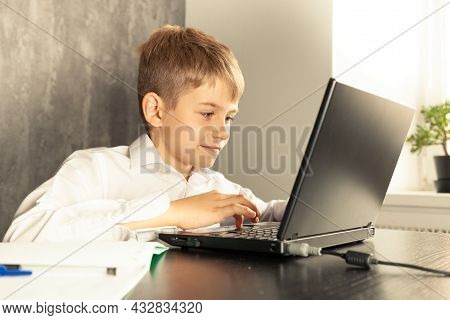 A Schoolboy Boy Studies At Home And Does School Homework.
