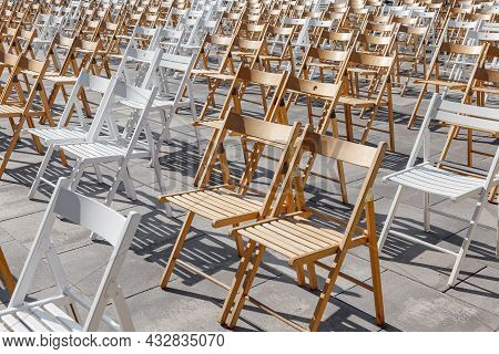 Folding Chairs Are Arranged In The Area For Outdoor Activities. Rows Of Empty Folding Wooden Chairs