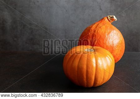 Two Ripe Whole Orange Pumpkins Of Different Grades On Black Background With Copy Space.