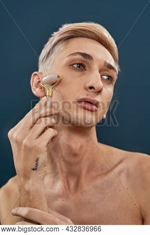 Portrait Of Androgynous Transgender Young Man With Light Hair Using Quartz Roller For Face Massage A