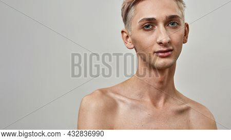 Portrait Of Shirtless Androgynous Transgender Young Man With Nude Makeup Looking At Camera While Pos