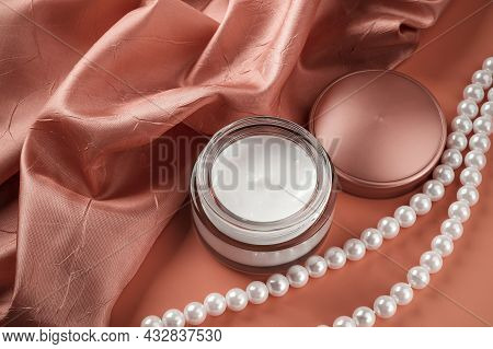 Beauty Skin Care Cream In An Open Glass Jar And White Pearl Beads Near Pale Burgundy Folded Silk Sat