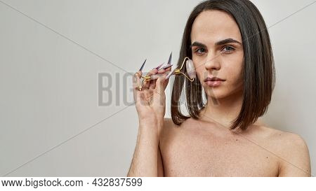 Androgynous Beautiful Young Transgender With Dark Brown Hairstyle Looking At Camera, Using Rose Quar