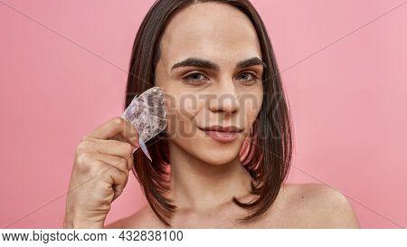 Closeup Of Pretty Young Transgender With Dark Brown Hair Using Rose Quartz Gua Sha Stone For Facial