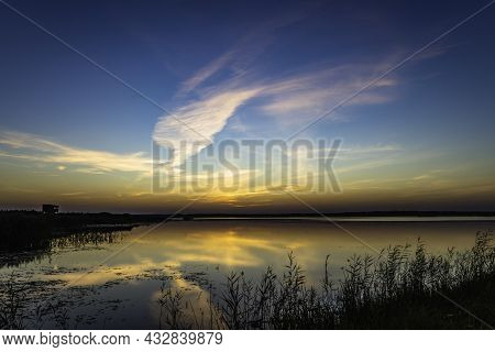 Dramatic Cloudscape With Symmetry Reflections On The Water Above The Lake At Sunrise