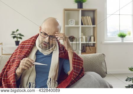 Sick Man Who Has Cold Or Flu Fever Takes His Temperature And Looks At Thermometer