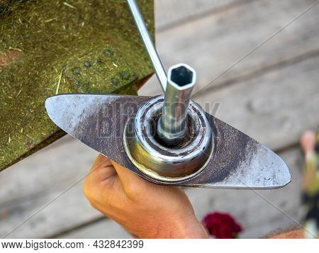 A Man Uses A Key To Unscrew The Blade On The Head Of A Gasoline Trimmer. Close-up, A Man At Work