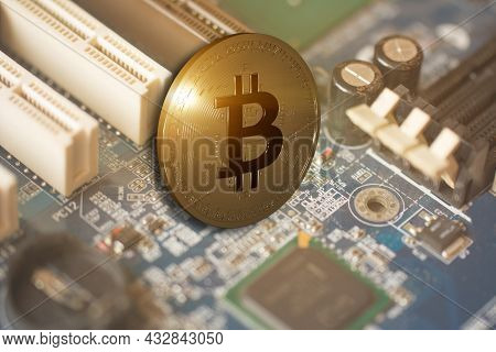 Bitcoin Gold Coin Against Computer Motherboard Background. Extraction Or Mining Virtual Cryptocurren