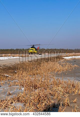 A Yellow Helicopter Takes Off From A Platform In The Remote Northern Area Of The Swampy Forest-tundr