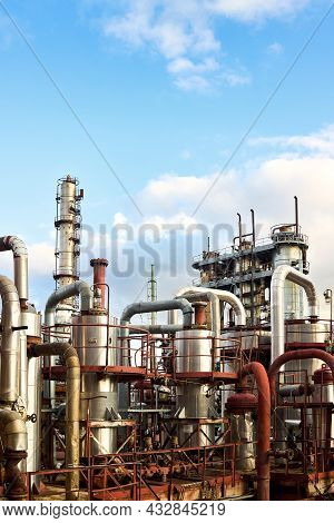 Old Distillation Column Towers Absorbers And Reactors Under Blue Evening Cloudy Sky Background At Ch