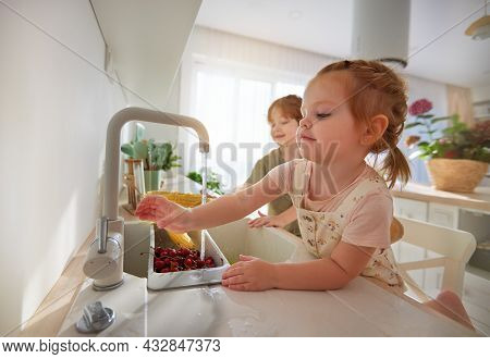 Cute Kids, Siblings Washing Corn And Cherries Under The Tap Water At The Kitchen At Home