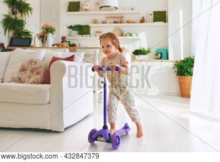 Happy Toddler Baby Girl Having Fun Riding Scooter At Home In Open Space Living Room
