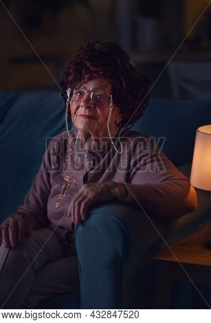 Portrait Of Elegant Mature Woman Sitting On Sofa At Home And Watching Tv At Night. 84 Years Old Woma