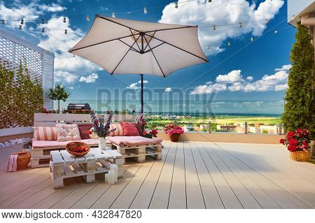 A Cozy Rooftop Patio With Wooden Pallet Furniture, Umbrella And Decking At Sunny Summer Day