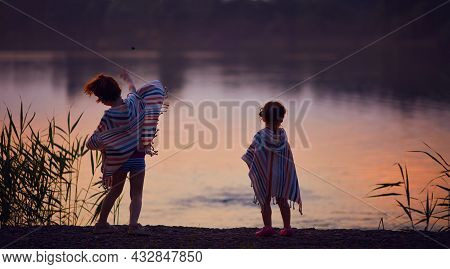 Cute Children, Siblings Throwing Stones In A Lake At Warm Summer Evening