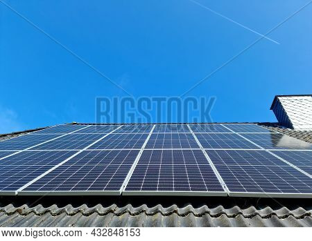 Solar Panels Producing Clean Energy On A Roof Of A Residential House With Black Roof Tiles.