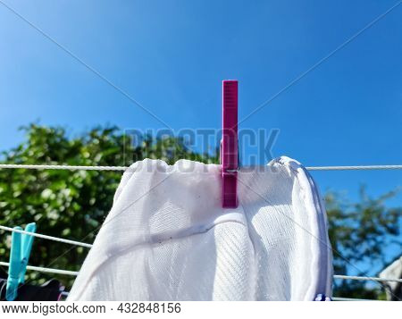 Clothes Hung Out On A Sunny Day To Dry On A Washing Line And Fastened By The Clothes Pegs..
