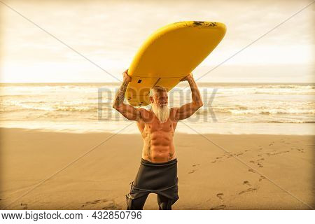 Happy Fit Senior Having Fun Surfing At Sunset Time. Sporty Bearded Man Training With Surfboard On Th