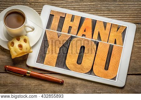 thank you - word abstract in vintage letterpress wood type on a digital tablet with coffee and cookie