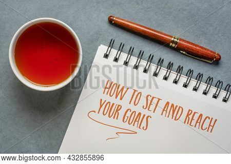 how to set and reach your goals, handwriting in a spiral notebook with a cup of tea, business and personal development concept