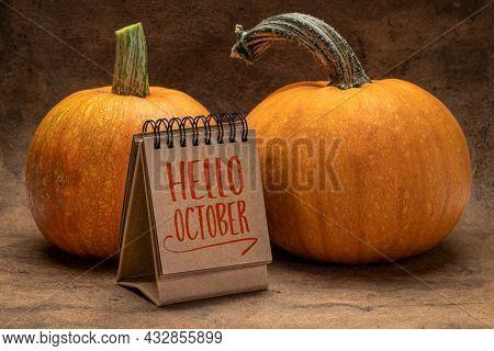 Hello October welcome note  - handwriting in a desktop calendar with pumpkins, fall season concept