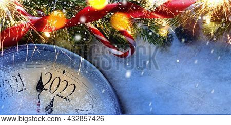 Countdown to midnight. Retro style clock counting last moments before Christmas or New Year 2022 next to decorated fir tree on snow. View from above.
