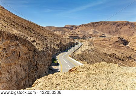 Israel. Excellent asphalt highway paved in the mountains. The ancient sandstone mountains of the Judean Desert surround the Dead Sea.