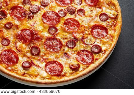 Tasty pepperoni and tomatoes on black background
