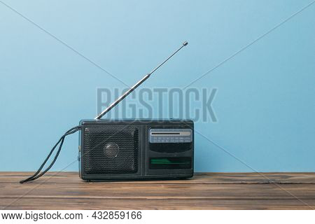An Old Black Radio On A Wooden Table On A Blue Background. Vintage Radio Equipment.