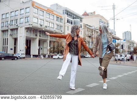Couple Of Playful Senior Women Have Fun Walking Along Contemporary City Street
