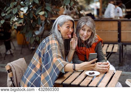 Mature Asian Woman Grimaces And Silver Haired Friend At Videochat In Street Cafe